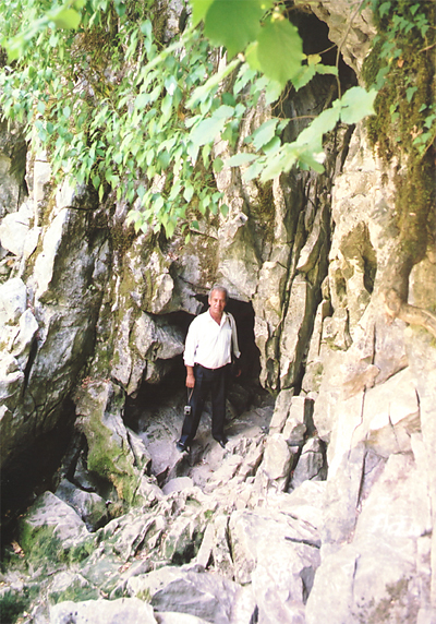 Nihat stands in front of the cave